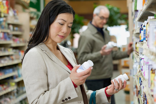 woman reading the label in a drug store