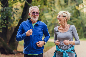 Photo sur Aluminium Jogging Cheerful active senior couple jogging in the park. Exercise together to stop aging.