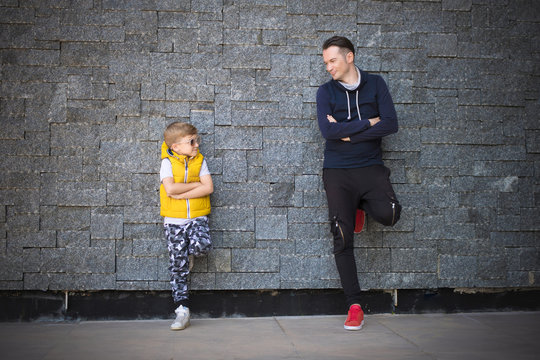 Full length of father and son talking while leaning on a wall.