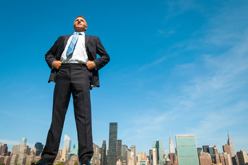 Giant businessman standing tall in dark suit above the city skyline Fotomurales