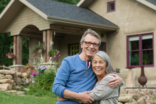 Portrait of senior couple outside country home
