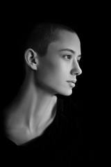 black and white portrait of fashion beautiful model, brunette girl with very short hair in studio, close up, young bold woman head shot