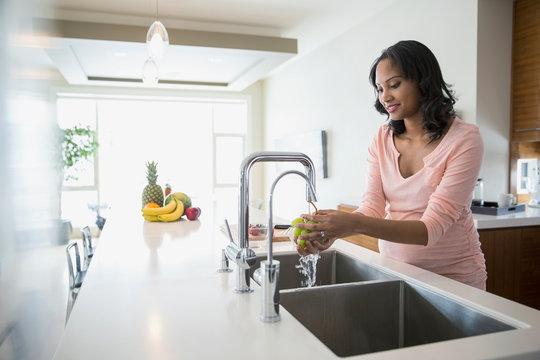Pregnant woman washing grapes at kitchen sink