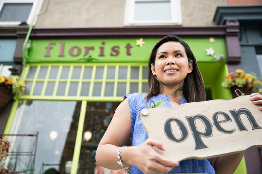 Female florist holding open sign in front of flower shop