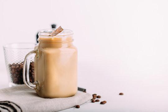 Glass mason jar with ice coffee with milk