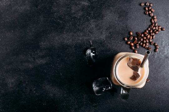 Glass mason jar with ice coffee with milk top view