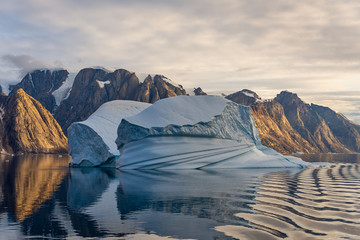 Beautiful view to iceberg at sunset from expedition vessel in Greenland fjord