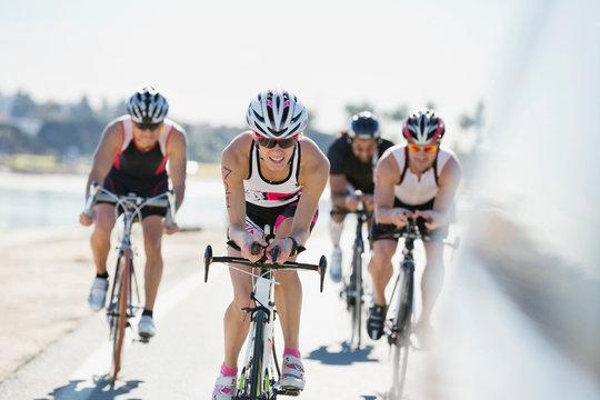 Group of triathlon cyclists racing on street