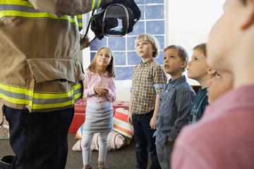 Firefighter giving presentation to elementary children