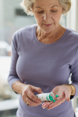 Senior woman with pills and pill bottle in hand