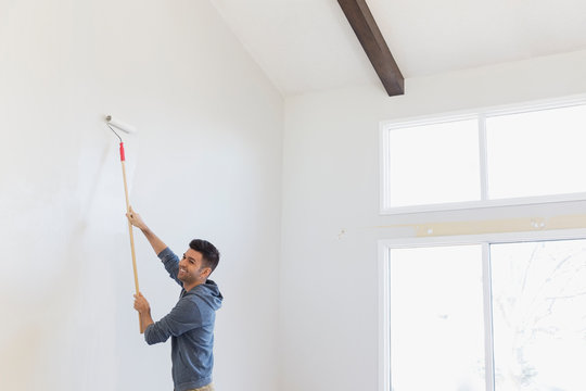 Smiling young man painting wall at home
