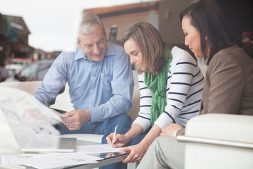Senior couple signing documents with financial advisor at home