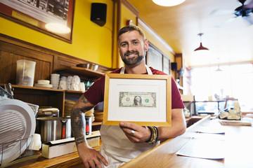 Portrait of male deli owner holding framed dollar bill