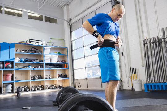 Man adjusting weight lifting belt