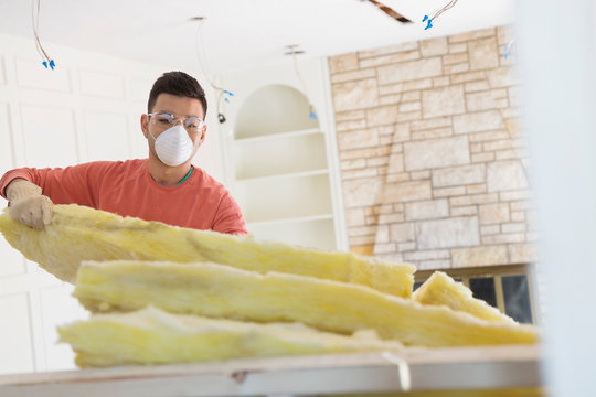 Young man installing insulation at home