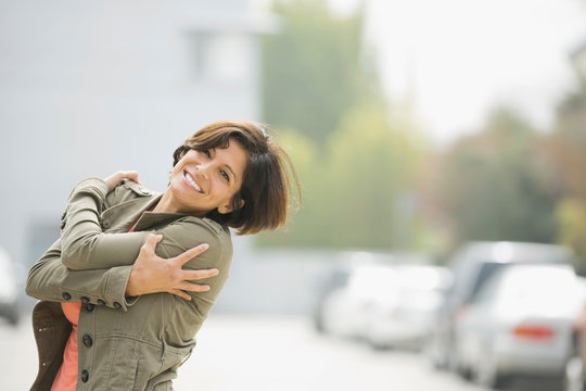 Smiling woman standing with arms around herself