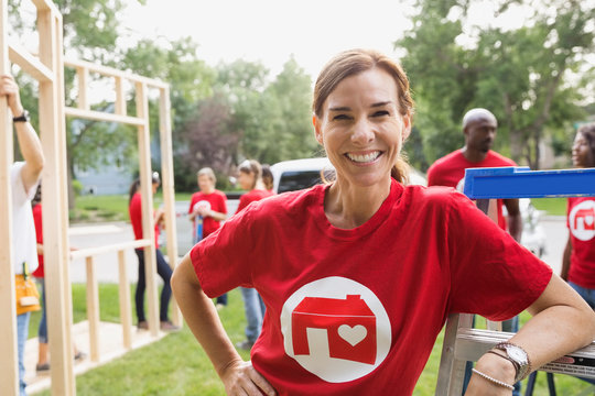 Portrait of confident volunteer near construction frame