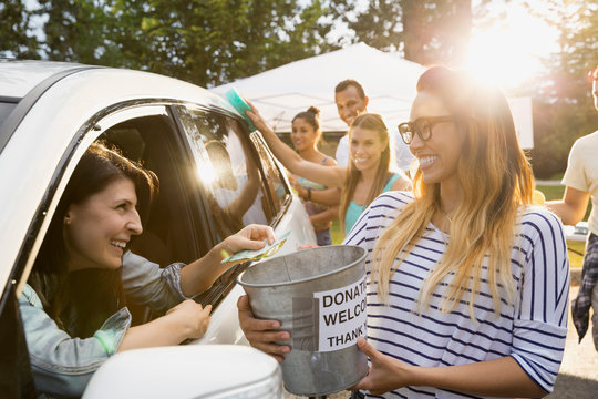 Woman donating money to charity car wash