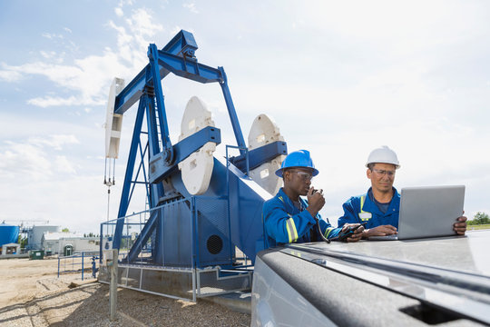 Male workers using laptop near oil well