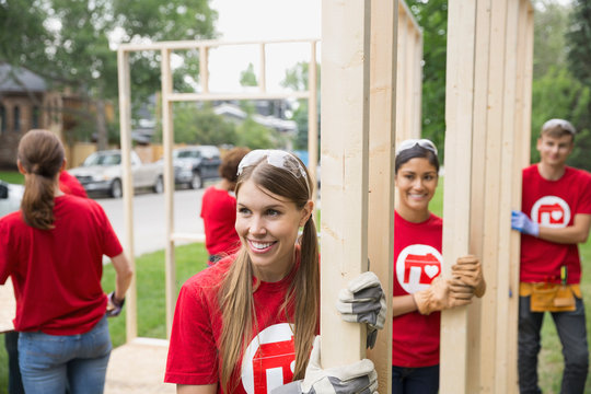Smiling volunteers carrying wood near construction frame