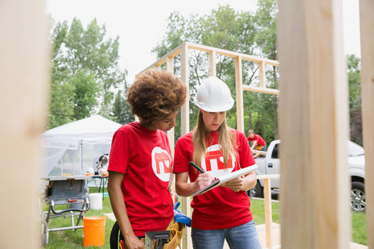Volunteers with notepad at construction frame