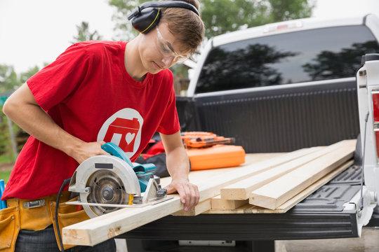 Volunteer using saw on wood on tailgate