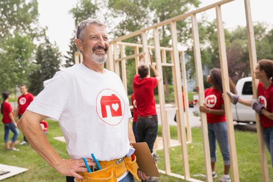 Volunteer with tool belt near construction frame