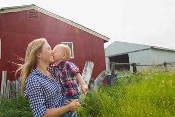 Son kissing motherŒÍŒ's cheek outside barn