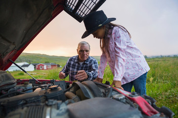 Grandfather and granddaughter examining truck engine