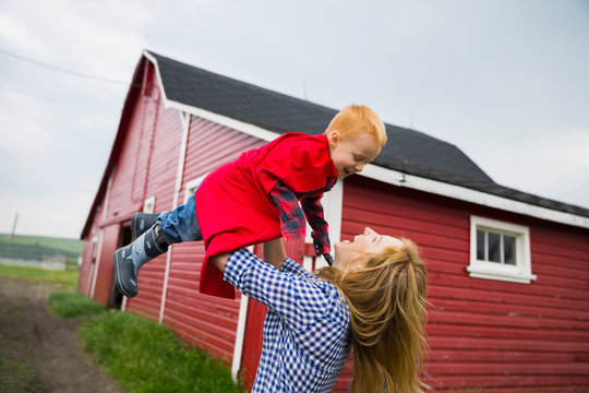 Mother lifting son in cape overhead outside barn