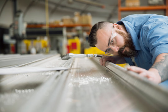 Worker examining sheet metal in manufacturing plant