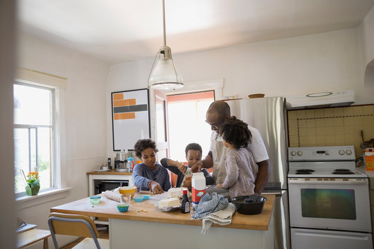 Father and children baking cake in kitchen