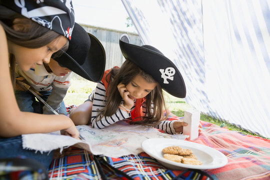 Children playing pirates with treasure map and cookies