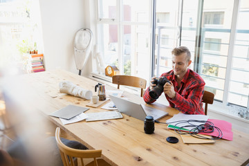 Photographer with camera uploading to laptop at tale