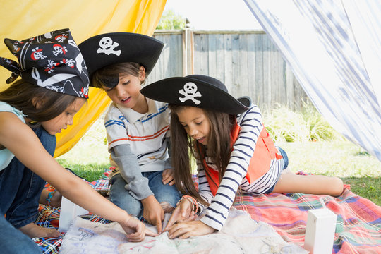 Children playing pirates and pointing at treasure map
