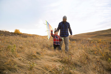 Father and son with kite walking in field