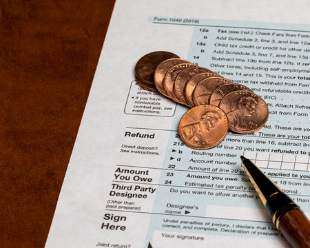 1040 individual income tax return form 2019 with ballpoint pen and pennies. Concept of filing taxes, payment, refund, and April 15, 2020 deadline date