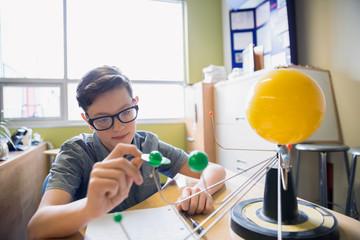 Elementary student examining solar system model