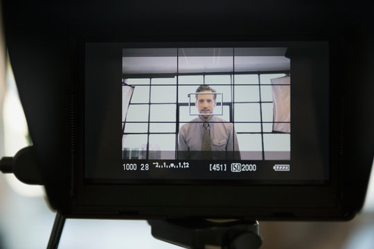 View of businessman from behind television camera