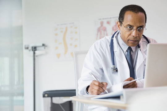 Male doctor taking notes in office