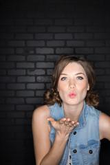 Portrait of brunette woman blowing a kiss