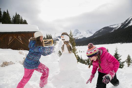 Girls enjoying snowball fight near snowman below mountains