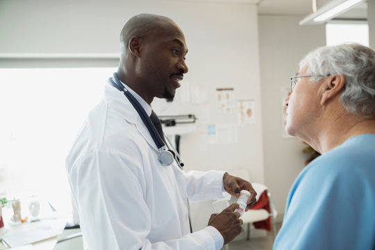 Doctor explaining prescription medication to senior man