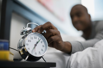 Man awaking to and turning off alarm clock