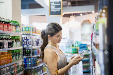 Woman reading label on bottle in grocery store