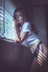 Sexy woman standing at the window