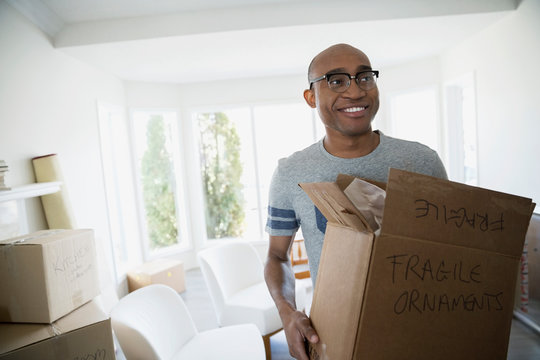 Smiling man carrying fragile moving box