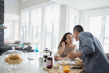 Couple kissing and preparing breakfast in kitchen