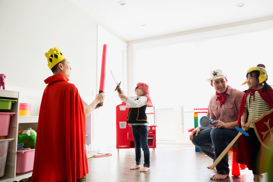 Father and daughter in costumes playing sword fight