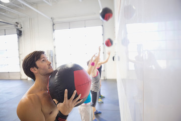 People practicing medicine ball wall throws